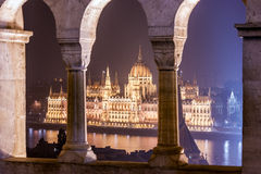Night view of the Hungarian Parliament Building. Between the columns of the fortress and viewpoint of the Fisherman's Bastion, located on the shore of Buda Stock Images