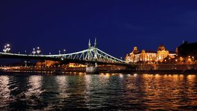Night View Of The Illuminated Freedom Bridge And The Embankment Of Budapest. View from the cruise ship floating on the Danube river near the bridge of freedom stock footage