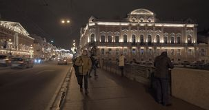 Nevsky Prospect and Anichkov Bridge in night St. Petersburg, Russia. Night view of illuminated Nevsky Prospect with transport traffic and people walking across stock footage