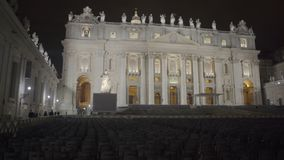 Night view of illuminated Saint Peter's Basilica facade, chairs for parishioners. Stock footage stock video footage