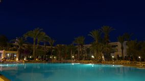 Night view of illuminated swimming pool near hotel building, timalapse. Night view of illuminated swimming pool with tourists walking near palm trees and hotel stock video footage