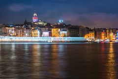 Night view of Istanbul cityscape Galata Tower with floating tourist boats in Bosphorus ,Istanbul Turkey stock photography