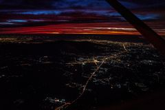 Night view from the jetplane in twilight time with the red sky and light of the city. Night view from the  jetplane in twilight time with the red sky and light stock photography