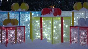 Large glowing holiday gift boxes lying in snow under Christmas tree stock video footage