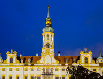 Night view of Loreta Facade. Night view of facade of Loreta church in Prague: green rooftop on white belfry, white walls, red rooftop Stock Photos