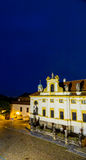 Night view of Loreta Facade. Night view of facade of Loreta church in Prague: green rooftop on white belfry, white walls, red rooftop Royalty Free Stock Image