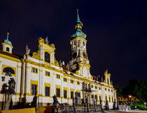 Night view of Loreta Facade. Night view of facade of Loreta church in Prague: green rooftop on white belfry, white walls, red rooftop Royalty Free Stock Photo