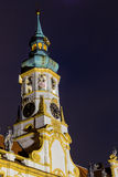 Night view of Loreta Facade. Night view of facade of Loreta church in Prague: green rooftop on white belfry, white walls, red rooftop Royalty Free Stock Photos