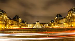 Night view of Louvre museum in Paris, with car lights trails. royalty free stock photo