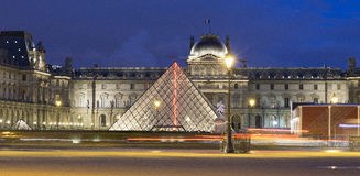 Night view on Louvre in Paris. Panorama with long exposure at night on part of the building of Louvre, Paris. red and white tales of lights across the image. in Stock Image