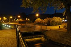 Night view of the Mill Island in Bydgoszcz, Poland. With cobbled sidewalks and a bridge across the river lit by yellow-orange sodium lanterns royalty free stock photos