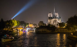 Night view of Notre Dame cathedral with Eiffel Tower searchlight Stock Photography