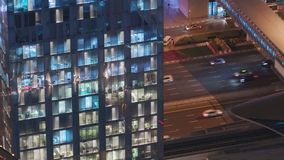 Night view of exterior apartment tower. High rise skyscraper with blinking lights in windows. Night view of office and apartment building with traffic on highway stock footage
