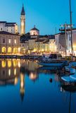 Night view of old city Piran in Slovenia. Beautiful cityscape through marina to Tartini Square. royalty free stock image