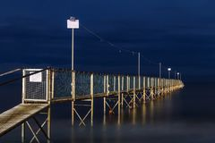 Night view of old wooden pier going into the sea. Adventure and challange concept royalty free stock image