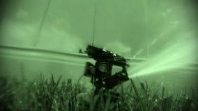 Night view oscillating lawn sprinkler watering grass