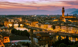 Night view over Arno river in Florence, Italy. Florence, Italy - skyline view over Arno river with Ponte Vecchio and Palazzo Vecchio at sunset stock photography