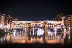 Night view of Ponte Vecchio bridge over Arno River. With water reflection in Florence, Tuscany, Italy Stock Images