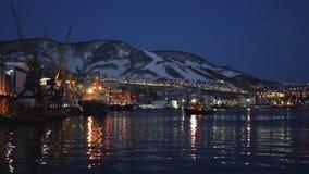 Night view of port tugboat docks to pier on seaport. PETROPAVLOVSK KAMCHATSKY CITY, KAMCHATKA PENINSULA, RUSSIAN FAR EAST - 21 APRIL, 2018: Night view of stock footage