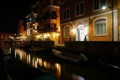 Night view of a quiet venetian canal with moored boats and street lights. With a distant outdoor restaurant terrace stock image