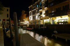 Night view of a quiet venetian canal with moored boats and street lights. With a distant outdoor restaurant terrace stock photography
