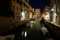 Night view of a quiet venetian canal with moored boats and street lights. And no people royalty free stock images