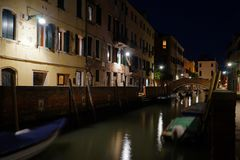 Night view of a quiet venetian canal with moored boats and street lights. And no people stock photo