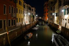 Night view of a quiet venetian canal with moored boats and street lights. And no people stock photos