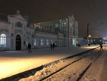 Night view of the railway station in the city of Cherepovets, Russia. People cross the rails in the light of lanterns royalty free stock photo