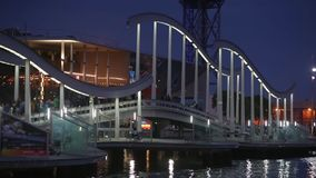 Night view of Rambla de Mar, footbridge modern design in the port of Barcelona. stock footage
