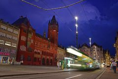 Night view of red Basel Town Hall at Marktplatz with a moving green tram on the designated track