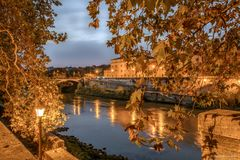 Night view of the river tevere in Rome. With a colorful sky and trees with autumn leaves under the yellow light of the street lanterns and lamp Royalty Free Stock Images