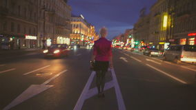 Night view of a road and backview of girl going at center of road stock video