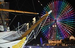 Night view of sailing boat and ferris wheel royalty free stock photos