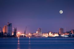 Night view of Savona. With sea foreground and Moon in the background Stock Photo
