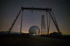 Night view. A special astrophysical observatory and a crane against the background of the starry sky Stock Images