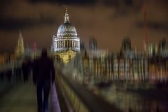 Night view of St Paul cathedral from the Millenium bridge in Lon. Night view of St Paul`s cathedral from the Millenium bridge in London, UK. Motion blur filter Royalty Free Stock Image
