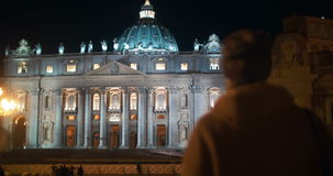 Night view of St. Peters Basilica in Vatican City. Steadicam shot of a woman coming towards St. Peters Basilica in Vatican City. Ancient church illuminated at stock video