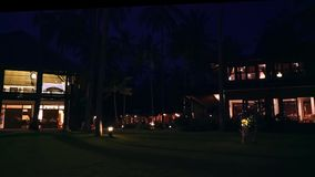 Night view of three wooden villas on lawn and between palm trees in Bali. Lights on. Shot with Sony a7s on a tripod stock footage