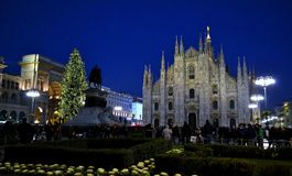 Night view to Duomo, tall illuminated Christmas tree and people walking. Royalty Free Stock Photos
