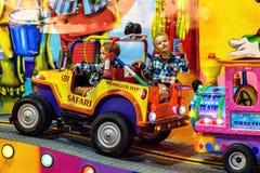 Night view to kids riding amusement cars on carousel. PROTARAS, CYPRUS - SEPTEMBER 23, 2017: Night view to kids riding amusement cars on carousel. Drawings on Stock Photos