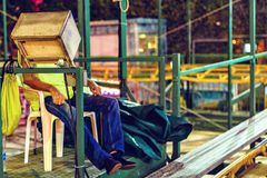 Night view to man sitting on chair near roller coaster control p royalty free stock photography
