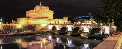 Night view to Saint Angel Castle and bridge under river Tiber at night in Rome, Italy. Bridge at night overlooking the Tiber river, and Angel fortress   by Royalty Free Stock Photo