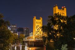 Night view of the Tower Bridge, Sacramento. Night view of the Tower Bridge connecting Sacramento to West Sacramento; downtown area skyline visible in the stock image