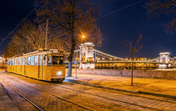 Night view of the tram on the background of the Chain Bridge in Budapest. BUDAPEST, HUNGARY - FEBRUARY 22, 2016: Night view of the tram on the background of the Royalty Free Stock Photos