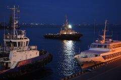 Night view of the tugboat in the cargo port of Odessa. Tugs and a floating crane are in port. Night panorama of the port royalty free stock image