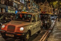 Night view with typical London taxis on moving in front of Harrods