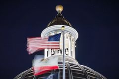 Night view of the US and the California state flag waving in the. Wind in front of the dome of the California State Capitol; Sacramento; long exposure stock photos