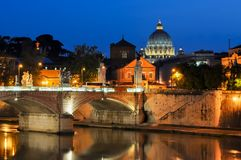 Night view of Victor Emmanuel bridge over Tiber river with St. Peter`s Cathedral dome at background, Rome, Italy Royalty Free Stock Image