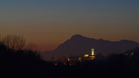 Night view of the village of Fagagna. Night view of the tower of the village of Fagagna with the Alps in the background, Friuli, Italy Stock Image